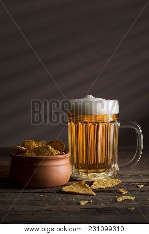 Mug Of Cold Pale Beer And A Bowl Of Tortilla Chips On A Rustic Wooden Table