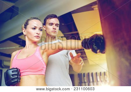sport, fitness, lifestyle and people concept - woman with personal trainer boxing punching bag in gym