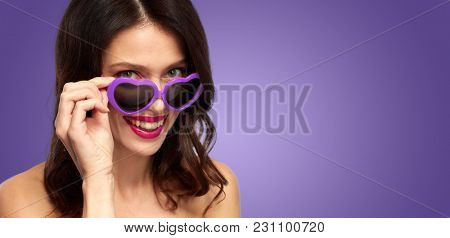valentines day, beauty and people concept - close up of happy smiling young woman with lipstick and ultra violet heart shaped sunglasses