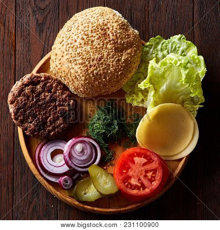 Yummy Hamburger Ingredients Artistically Organized On Wooden Plate Over Rustic Vintage Background, C