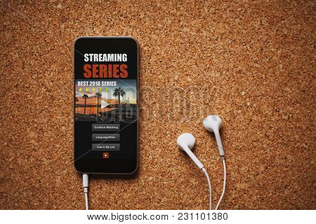 Front View Of Streaming Series App In A Mobile Phone Screen, Close To White Earphones On A Brown Tab