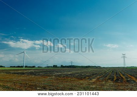 Wind Turbines For Electrical Power Generation In Agricultural Fields. Countryside In Normandy, Franc