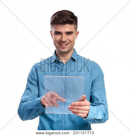 young casual student working on a futuristic transparent touchscreen tablet like gadget on white background
