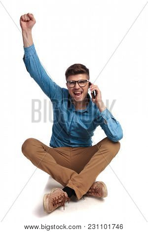 seated casual man talking on the phone is celebrating success with hand in the air on white background