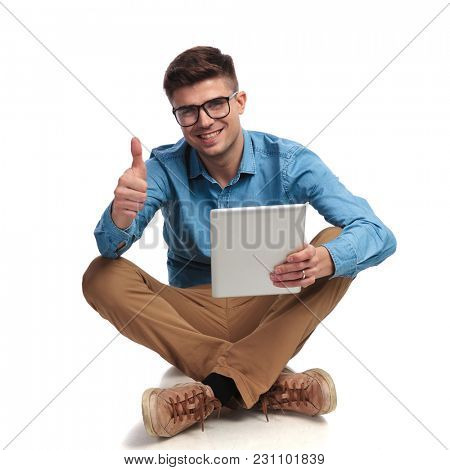 seated casual student reading good news on tablet and makes ok sign on white background