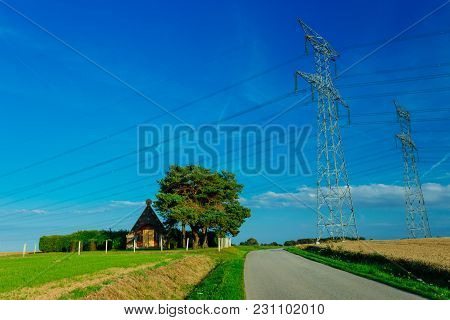High Voltage Power Lines And Transmission Towers In Normandy, France. Countryside Landscape, Asphalt