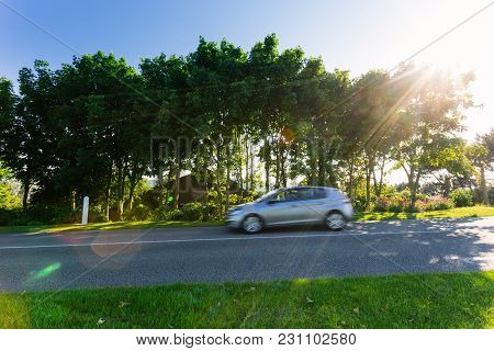 Cars Driving On The Asphalt Road Passing Through Green Agricultural Fields On A Sunny Day In Normand
