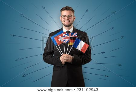 Smiling young man standing with flag and multidirectional arrows around
