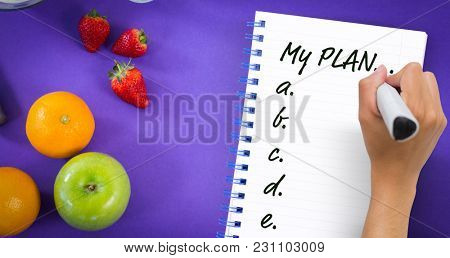 Hand writing with marker against overhead ciew of various fruits