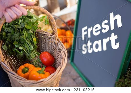 Fresh start against hand holding a basket full of vegetables in a market