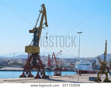 18.06.2018, Crete, Greece: Cargo Cranes And Ship In The Sea Port Over Blue Sky Background