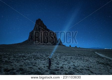 Hiker With A Head Lamp Under The Night Sky With Many Stars Near Shiprock. Shiprock Is A Great Volcan