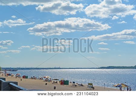 Samara, people on city beach on the shores of the Volga River. beautiful cumulus clouds on blue sky poster