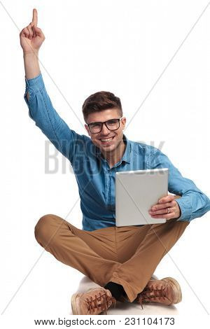 happy casual man pointing finger up while holding tablet and sits on the floor on white background