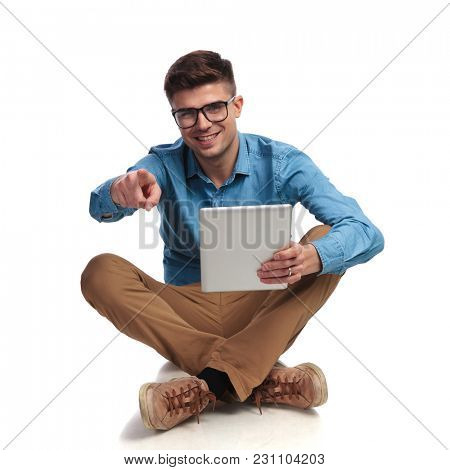 young casual student reading on tablet and points finger while sitting on the floor on white background