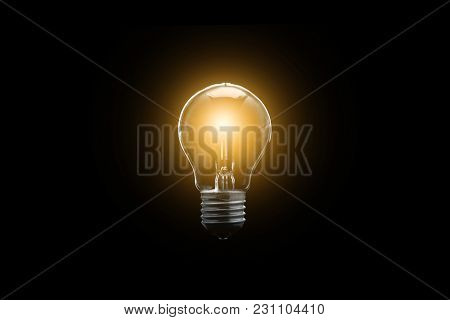 The Electric Bulb Is Glowing On A Dark Background. The Concept Is A Successful Idea.