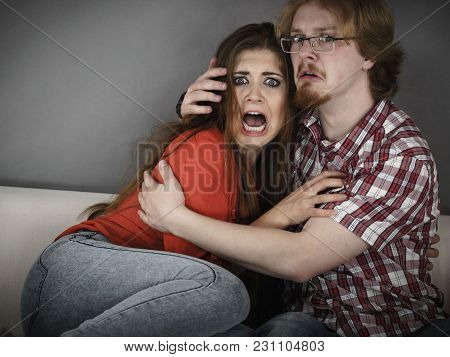 Funny Couple Sitting On Sofa Watching Horror Movie Being Scared Hugging Each Other.
