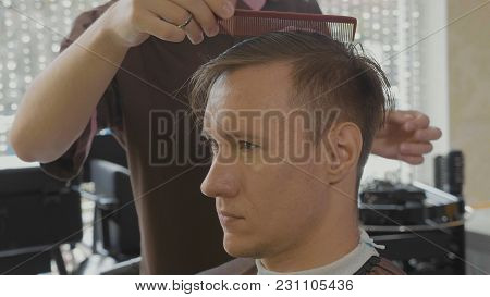 Barber Does Hairdo After Haircut. Close-up Of Hairdresser Combs Male Client By Hand After Haircut.