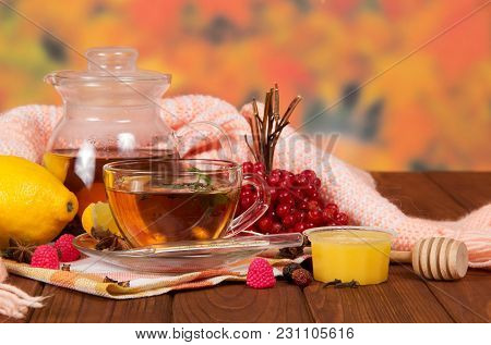 Pitcher And Cup Of Tea, Berries, Fruit, Honey For Colds, Warm Scarf And Thermometer On Wooden Table
