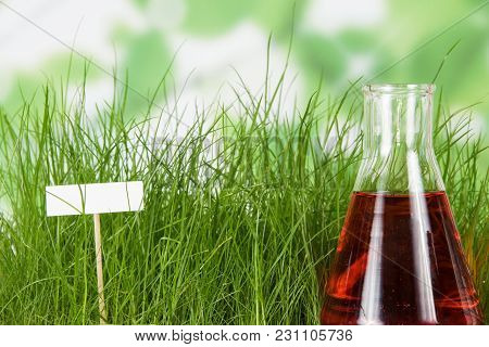 Flask With Liquid Fertilizer On Background Of Green Grass And Blank Card For Writing