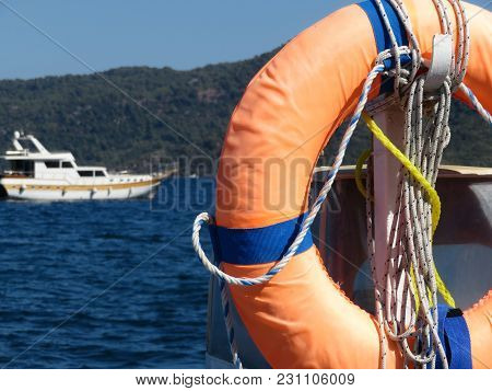 Orange Lifebuoy On The Sea Background. Lifeline Hanging On The Pier. Rescue Boat On The Sea