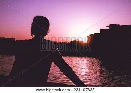 Black Silhouette Of A Young Girl Looking At The River And Surreal Landscape With Purple Sky