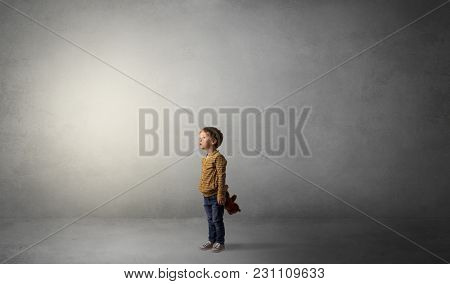 Little waggish kid staying alone in a big empty room with his plush