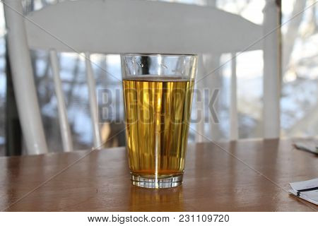 Craft Beer In Pint Glass On Wood Table. White Chair In Front Of Window. View Out Window Of Snow And
