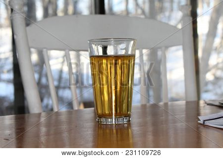 Craft Beer In Pint Glass On Wood Table. White Chair And View Out Window Of Woods And Snow