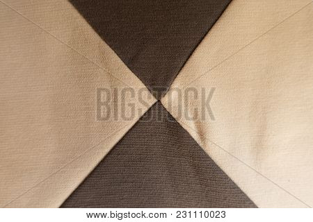 Four Triangular Pieces Of Beige And Brown Fabrics Sewn Together
