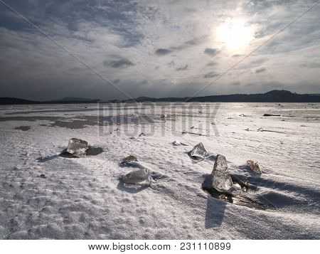 Melting Ice Crystals And Icebergs. The Beach Covered By Thick Ice In Winter Time.