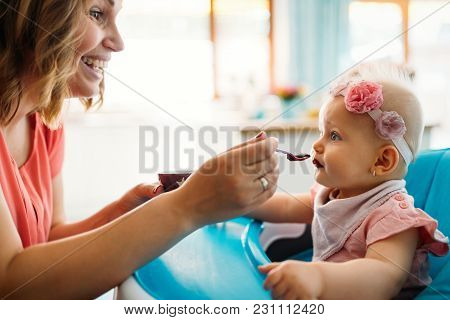 Mother Feeding Baby With Spoon Indoors