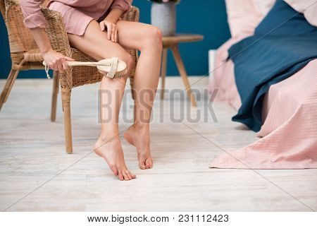 Woman Brushing Legs With Body Brush Sitting On The Chair At Home