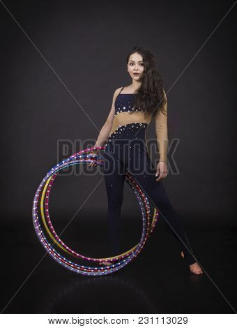 Gymnastic Exercises With Hula-hoop Girl Performs Circus Performer In An Artistic Costume. Studio Sho