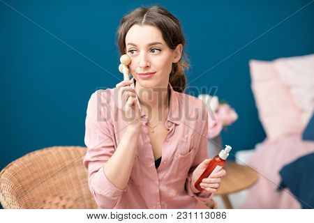 Young Woman Applying Facial Massage With Wooden Rolls Sitting On The Blue Wall Background At Home