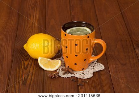 Cup Of Hot Tea With Lemon And Spices From Colds, On Brown Wooden Table