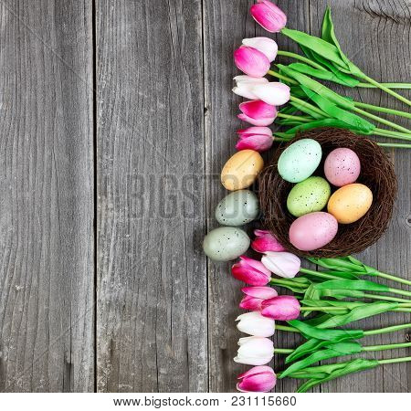 Pink Tulips And Colorful Eggs On Vintage Wooden Planks For Easter Background