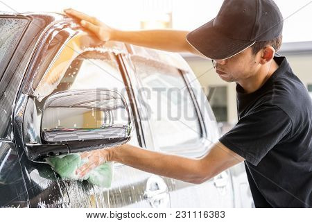 Car Wash Worker Wearing A T-shirt And A Black Cap Is Using A Sponge To Clean The Car In The Car Wash