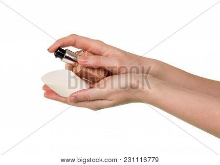 Vial With Foundation Cream And Sponge In Female Hand Isolated On White Background
