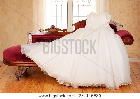 Tulle Wedding Dress Laying On Chaise Lounge