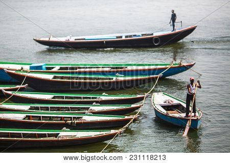 VARANASI, INDIA - MAR 13, 2018: Boatmen on the banks of Ganga river. Varanasi is one of the most important pilgrimage sites in India and is one of the 7 sacred cities of Hinduism.