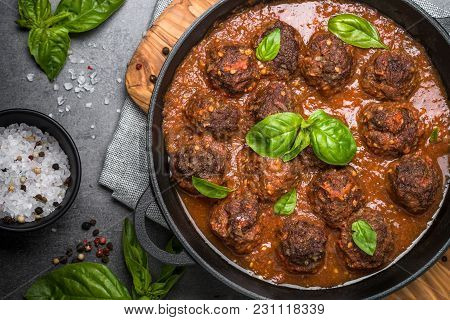Meatballs In Tomato Sauce In A Cast-iron Frying Pan On Black Background. Top View.
