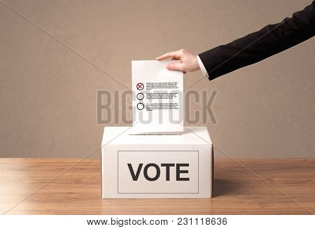 Close up of male hand putting vote into a ballot box, on grungy background