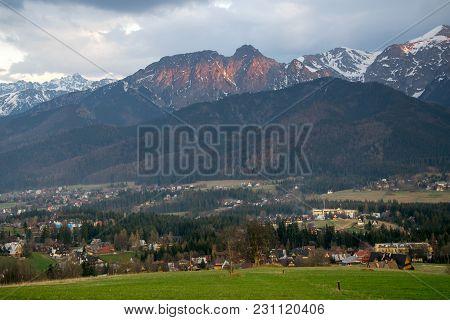 Scenic View Of Koscielisko Village Near Zakopane With Panorama Of Snow Caped High Tatras And Giewont