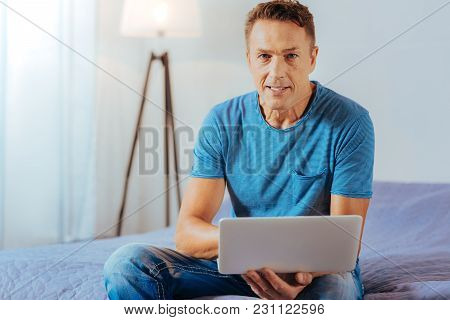 Portable Device. Positive Nice Handsome Man Sitting At Home And Holding A Netbook While Using Modern