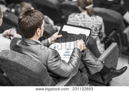 Rear View:businessman With Financial Documents Sitting At The Lecture Hall. Business Trainings And B