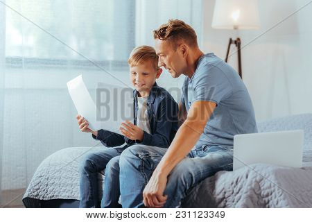 So Beautiful. Delighted Nice Positive Man Sitting On The Bed And Looking At His Sons Drawing While E
