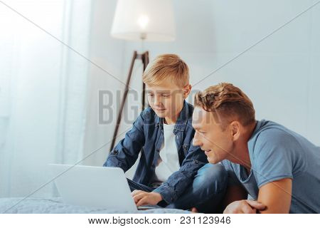 Digital Device. Joyful Positive Nice Man Lying On The Bed And Looking At The Laptop Screen While Bei