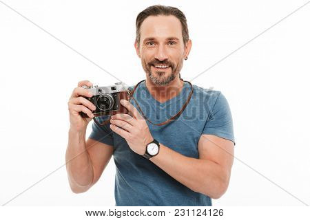 Portrait of a smiling mature man dressed in t-shirt holding photo camera isolated over white background