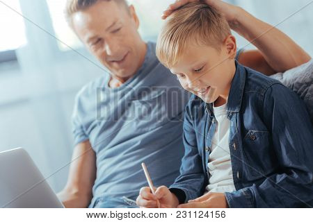 Preparation For School. Joyful Nice Smart Boy Sitting Together With His Father And Taking Notes Whil